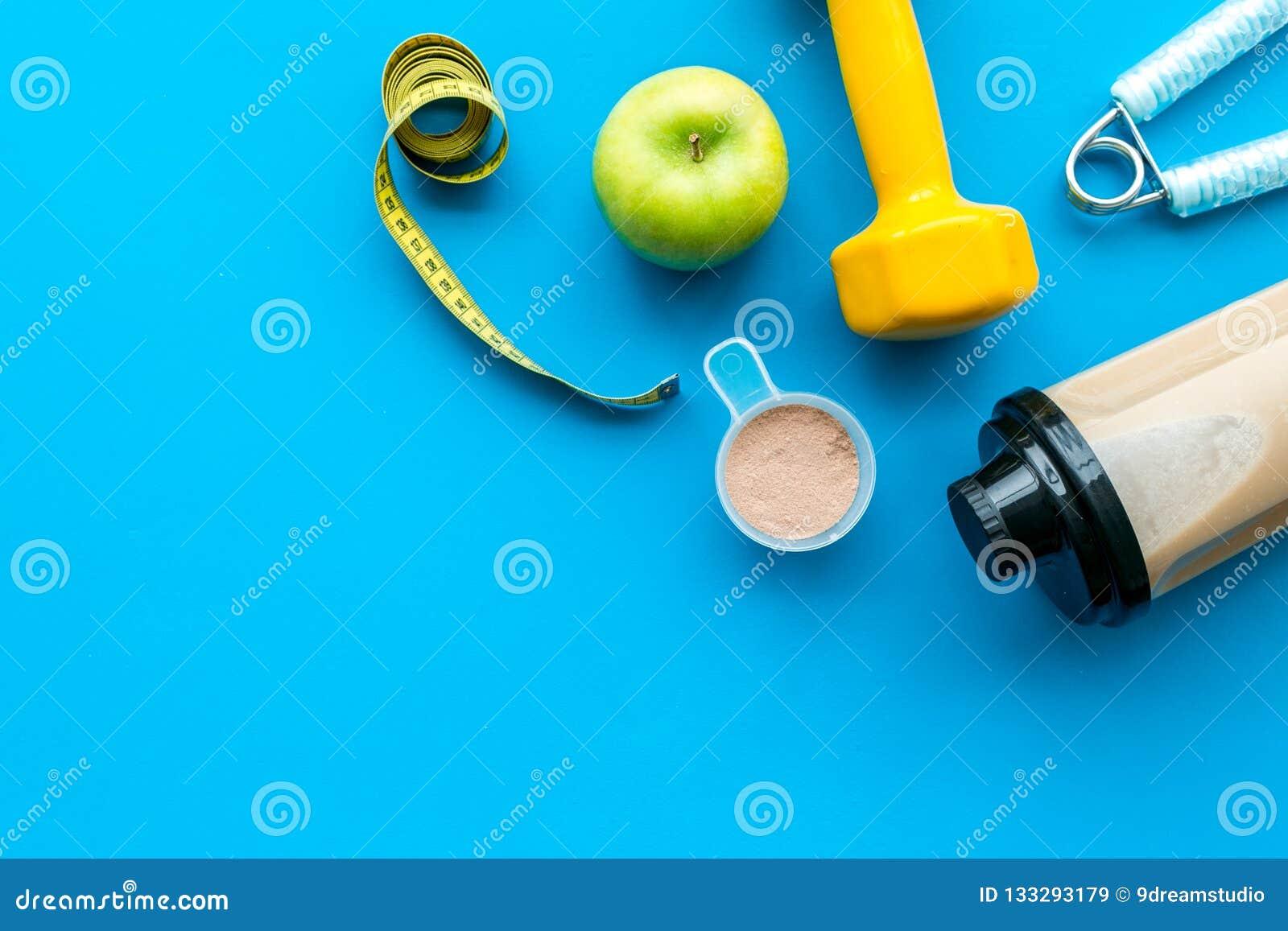 Διατροφή για το workout με το πρωτεϊνικό κοκτέιλ και τους φραγμούς στο μπλε πρότυπο άποψης υποβάθρου τοπ
