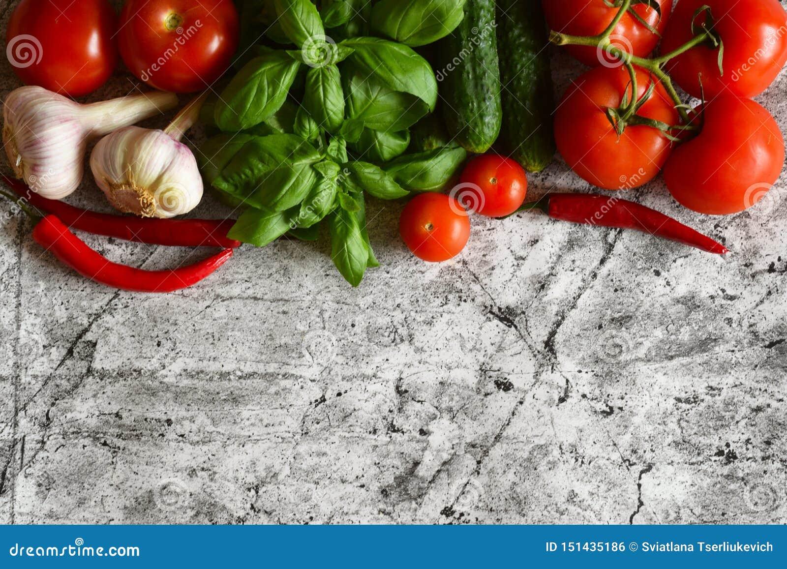 Διαφορετικά λαχανικά σε ένα όμορφο υπόβαθρο: ώριμες ντομάτες, αγγούρια, σκόρδο, ευώδης βασιλικός, καυτά πιπέρια