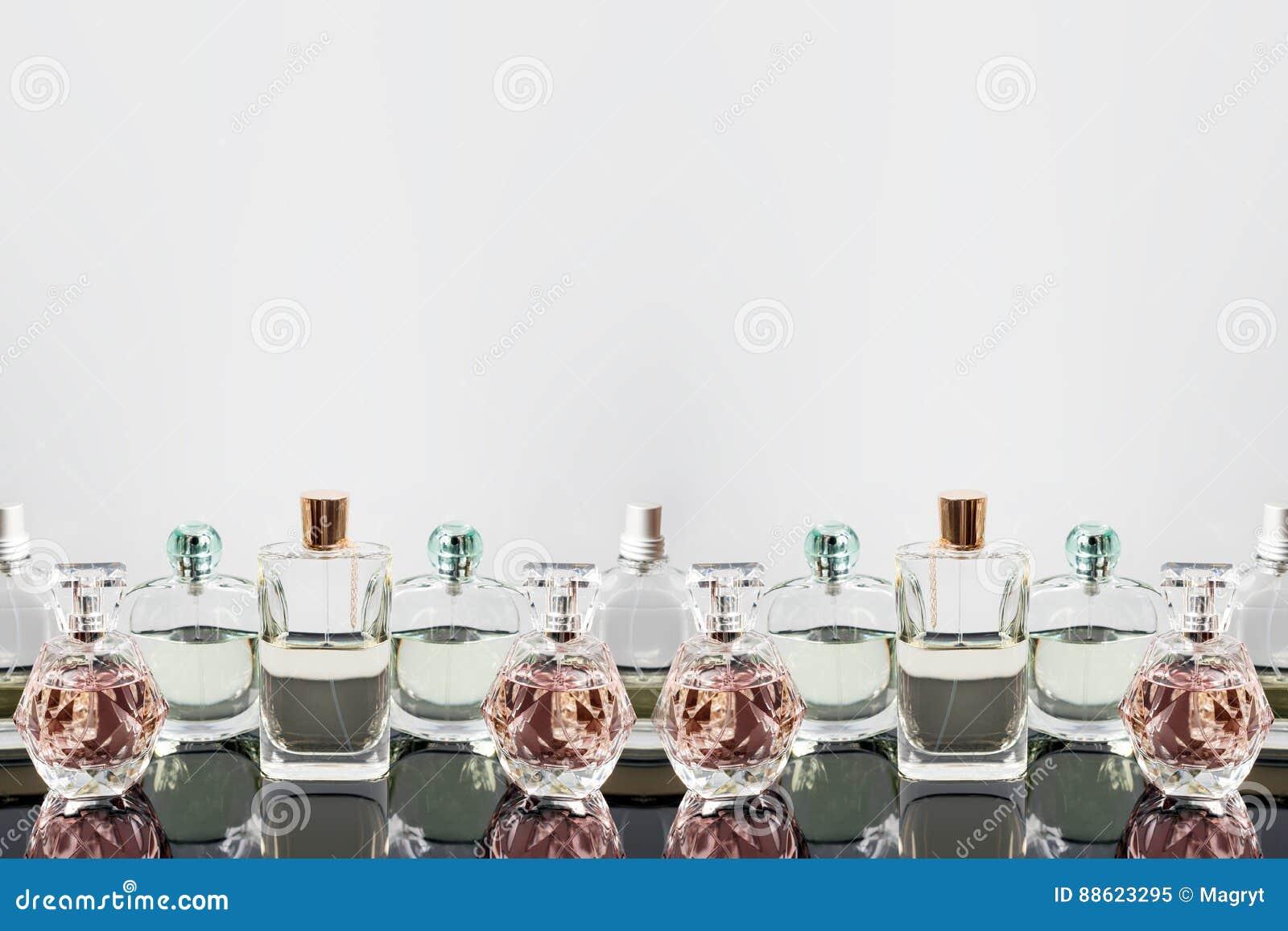 Διαφορετικά μπουκάλια αρώματος με τις αντανακλάσεις Αρωματοποιία, καλλυντικά Ελεύθερου χώρου για το κείμενο