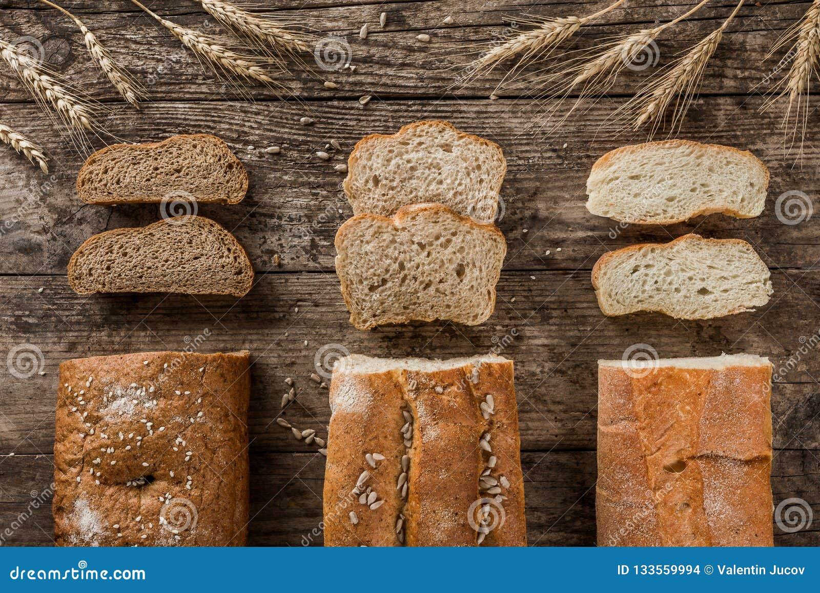Διαφορετικά φρέσκα ψωμί και spikelets του σίτου στο αγροτικό ξύλινο υπόβαθρο Δημιουργικό σχεδιάγραμμα φιαγμένο από ψωμί