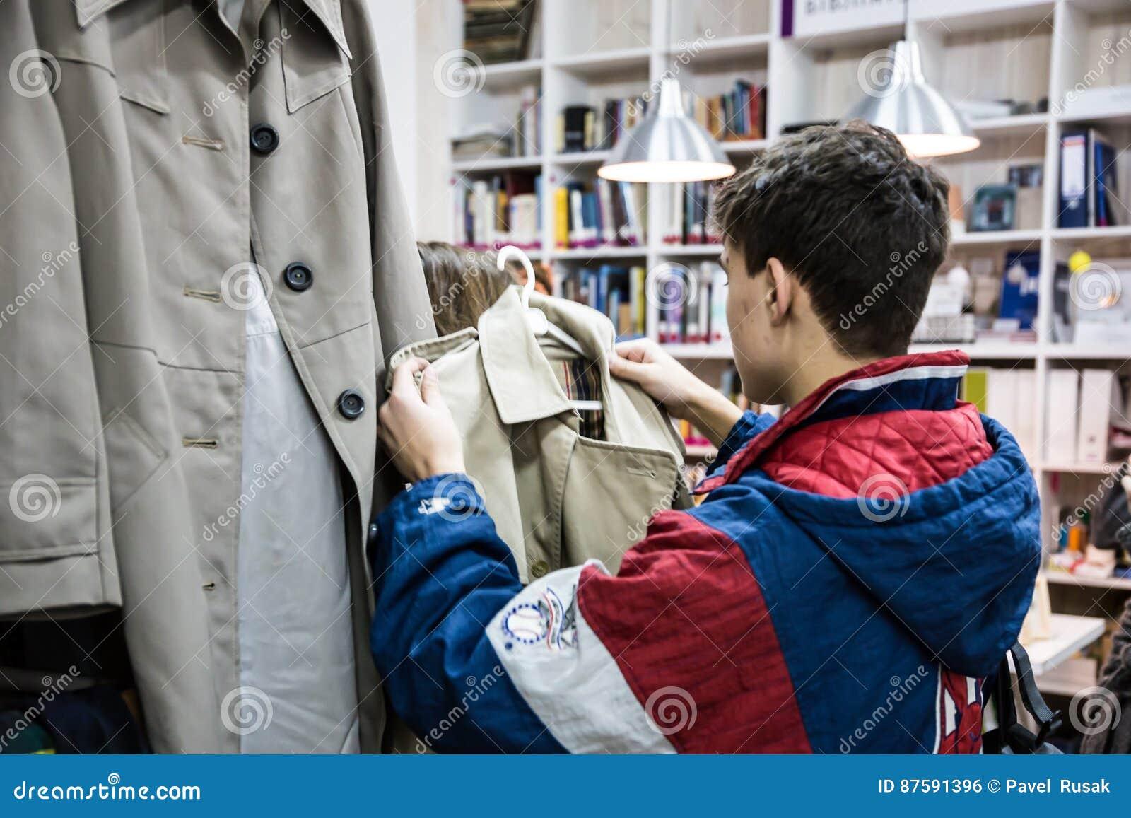 7daccdfa414c Διαφορετικές ενδύματα και τσάντες στα ράφια και κρεμάστρες στο κατάστημα