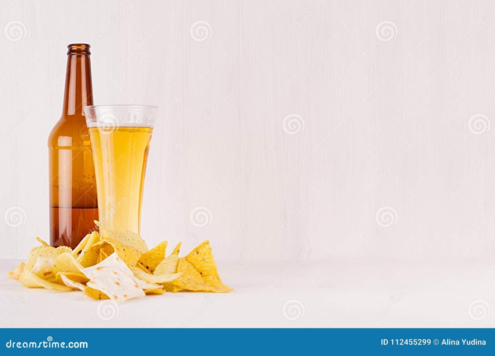 Διαφορετικές τριζάτες χρυσές πρόχειρα φαγητά και μπύρα σωρών στο γυαλί, καφετί μπουκάλι στο μαλακό άσπρο ξύλινο υπόβαθρο, με το δ