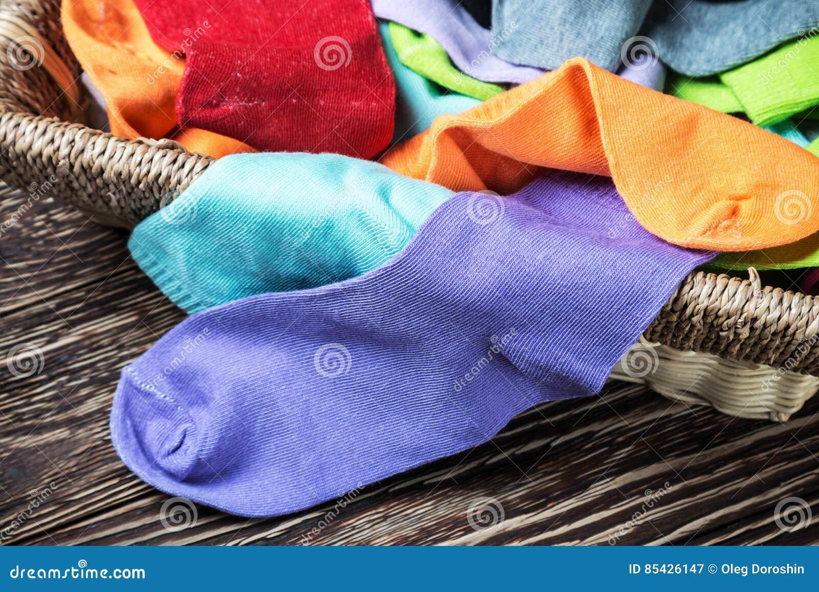 Διαφορετικές υφαντικές κάλτσες χρώματος στο καλάθι