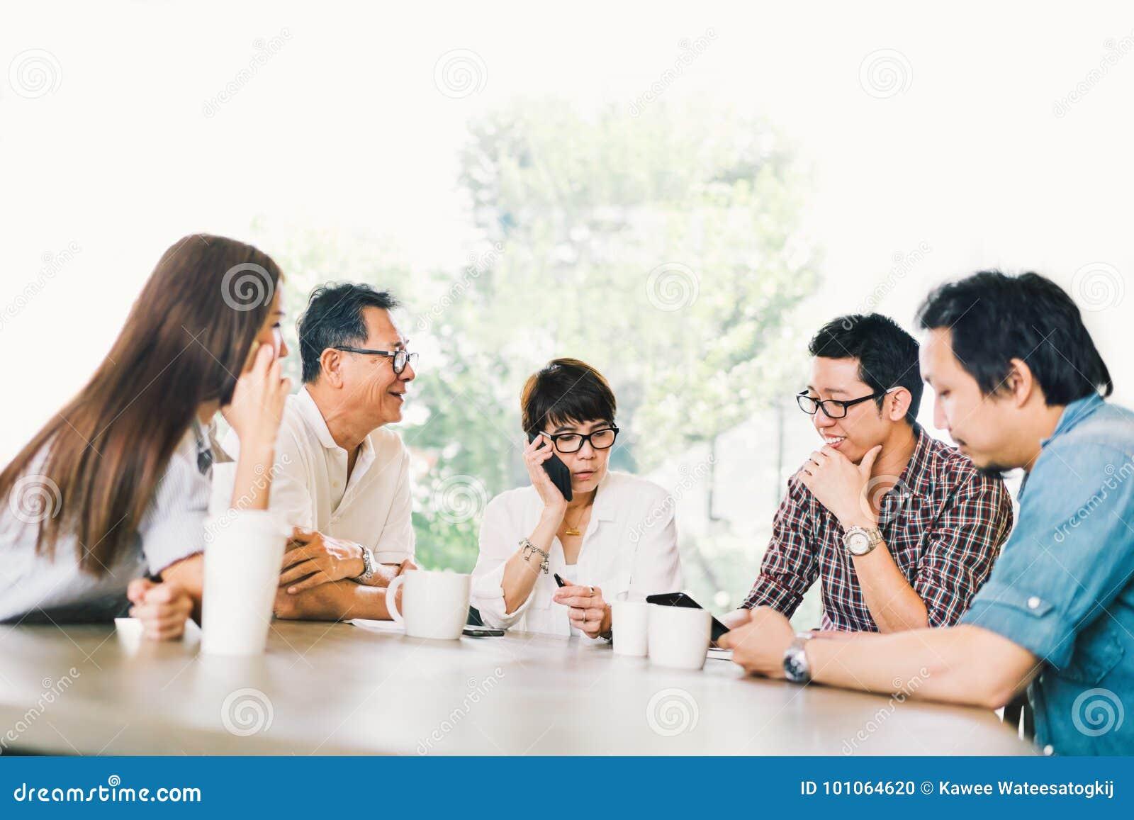Διαφορετική ομάδα ασιατικού επιχειρησιακού πέντε προσώπου στη συνεδρίαση των ομάδων στη καφετερία ή το σύγχρονο γραφείο Στρατηγικ