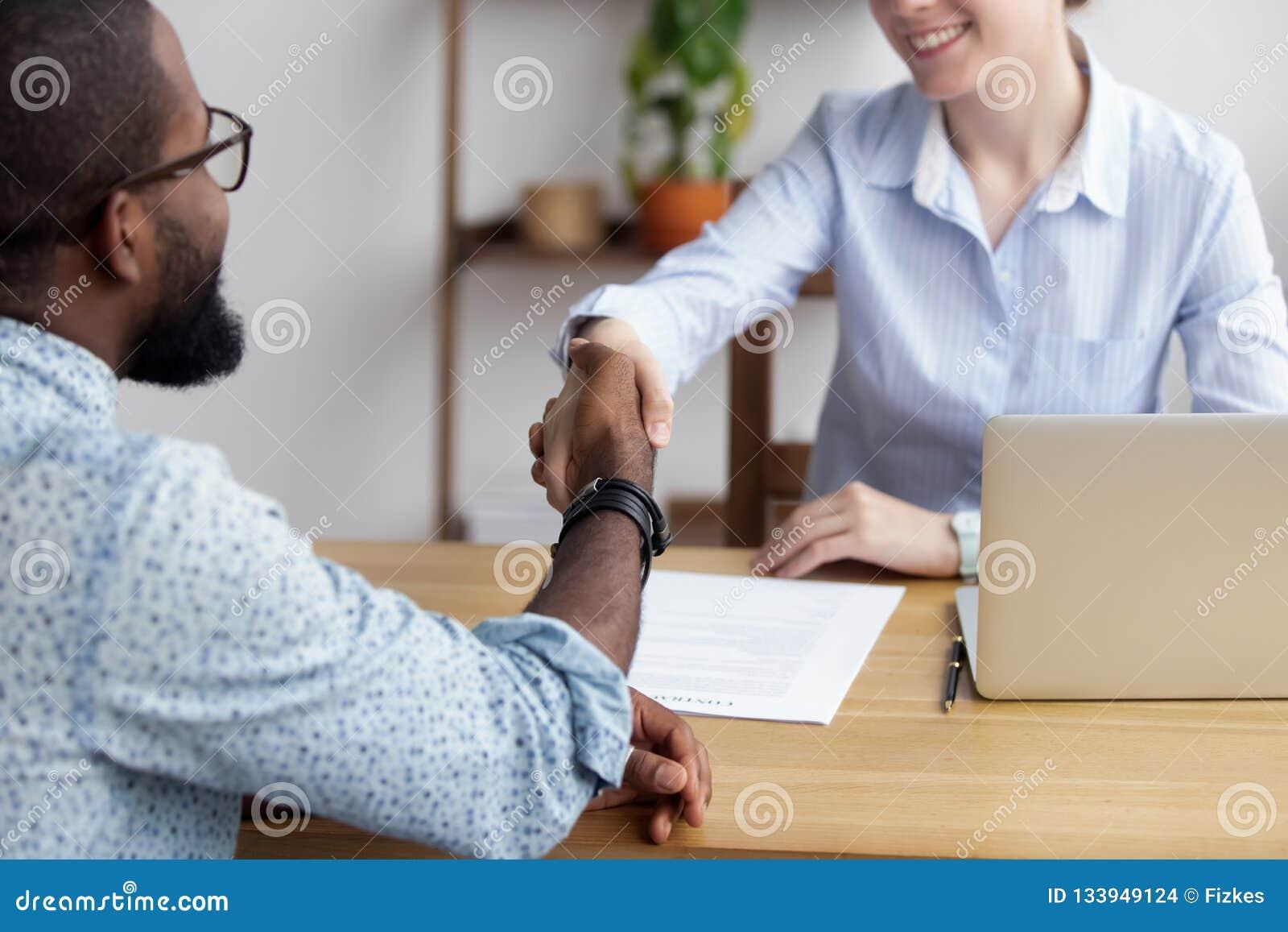 Διαφορετικοί επιχειρηματίες που τινάζουν τα χέρια που χαιρετούν το ένα το άλλο