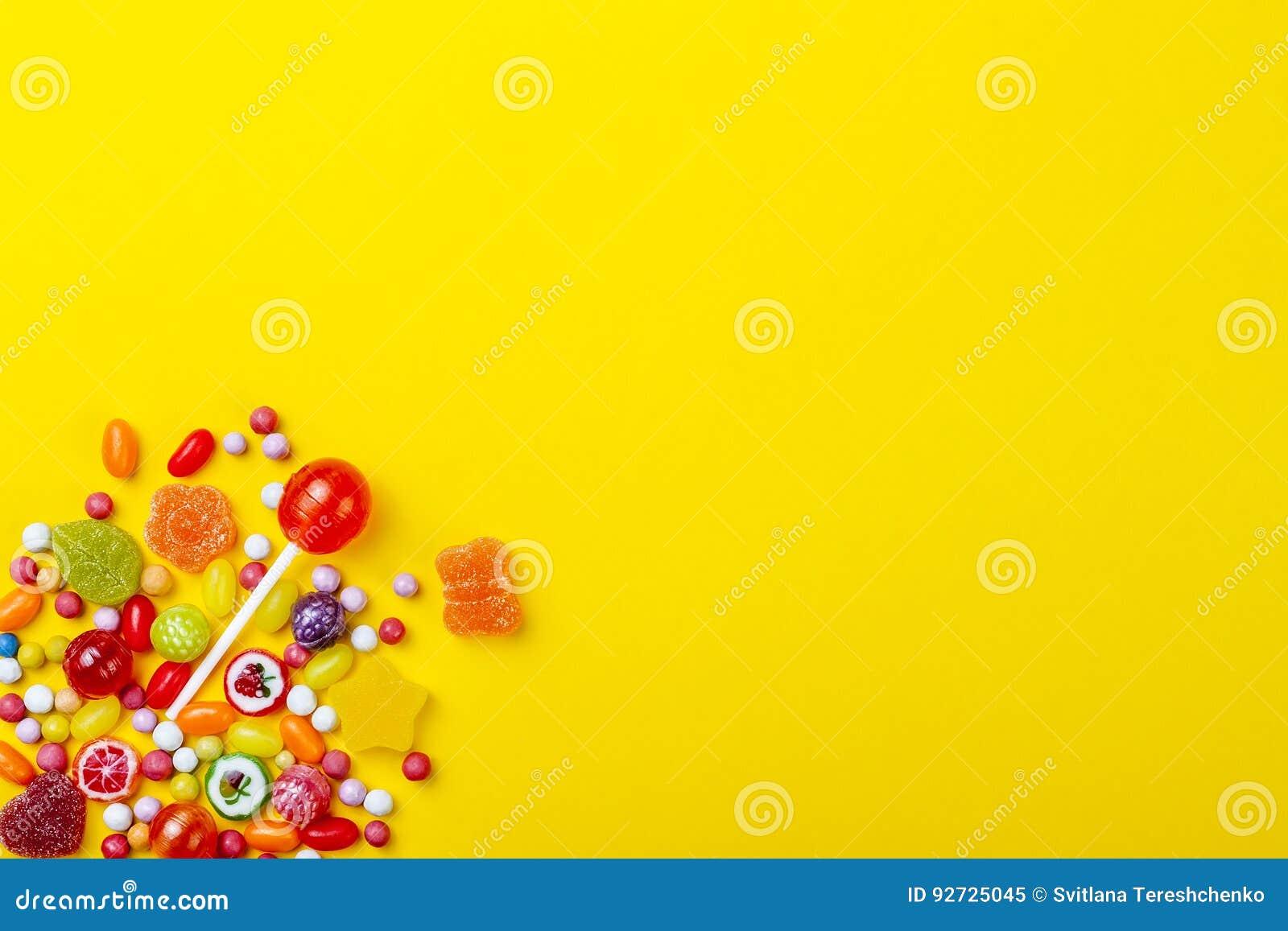 Διαφορετικοί τύποι καραμελών στο κίτρινο υπόβαθρο, διάστημα αντιγράφων