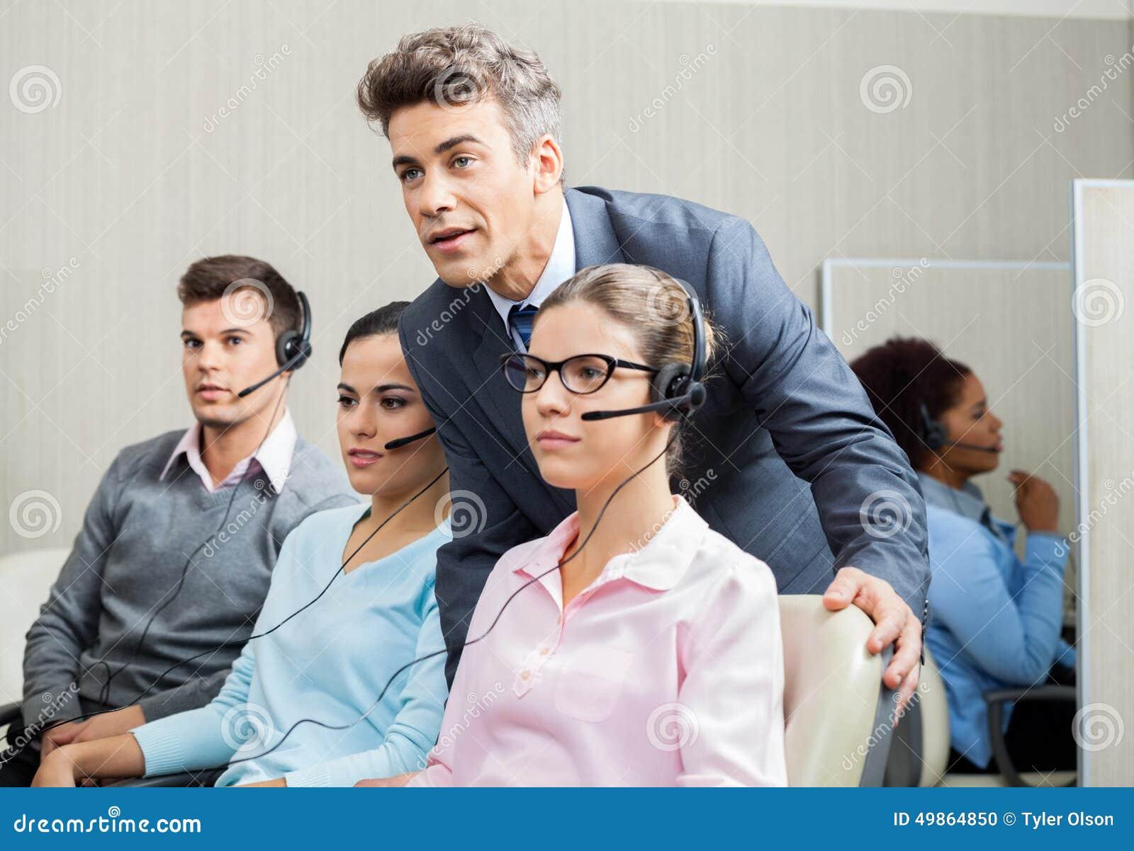 Διευθυντής που εξηγεί στον υπάλληλο στο τηλεφωνικό κέντρο