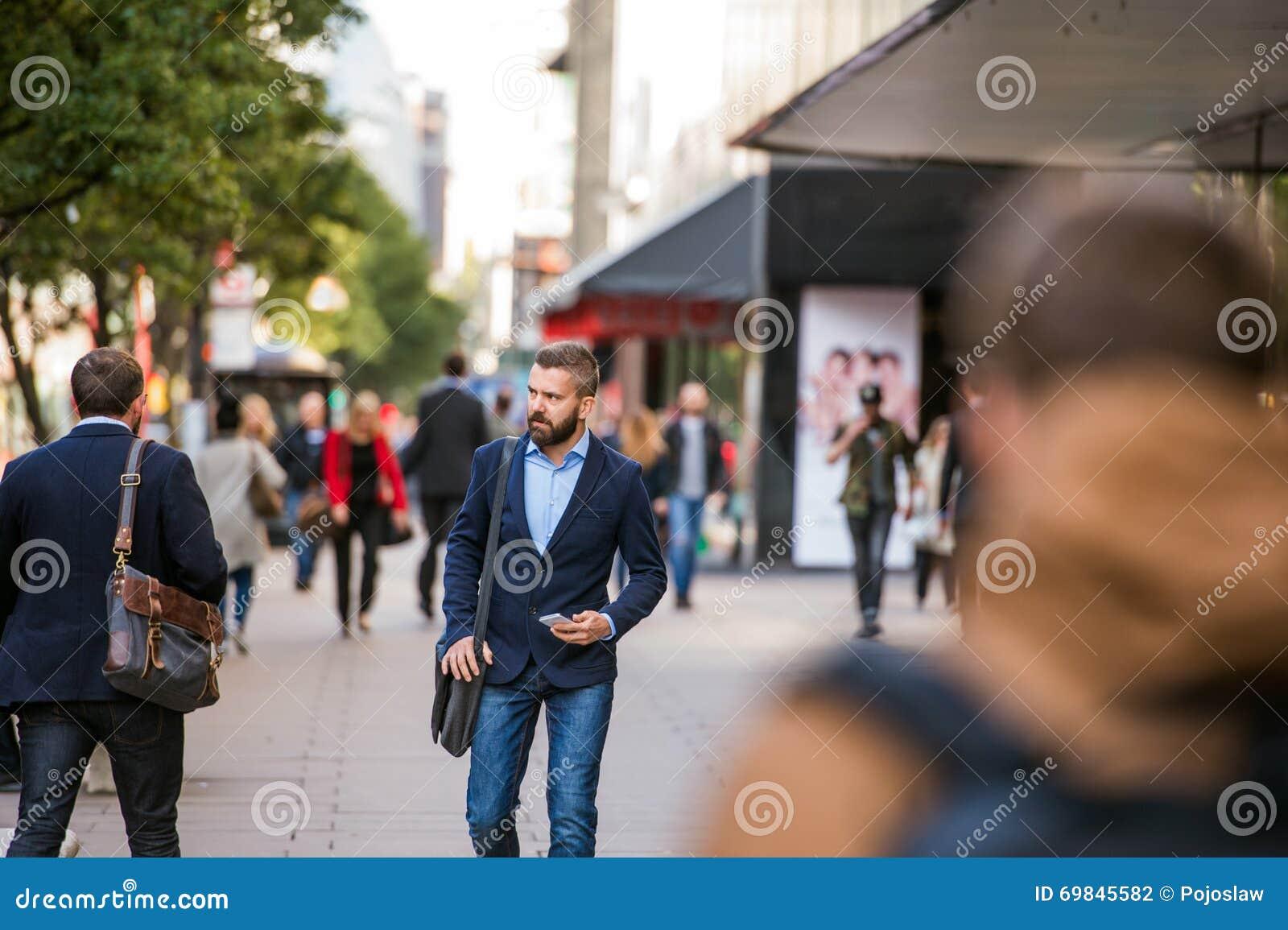 Διευθυντής Hipster με το έξυπνο τηλέφωνο που περπατά στην οδό