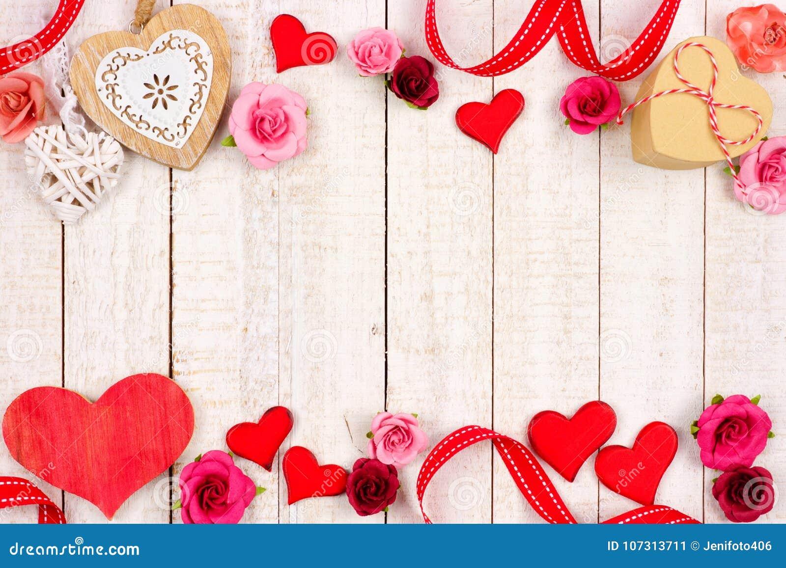 Διπλά σύνορα ημέρας βαλεντίνων των καρδιών, των λουλουδιών, των δώρων και του ντεκόρ στο άσπρο ξύλο