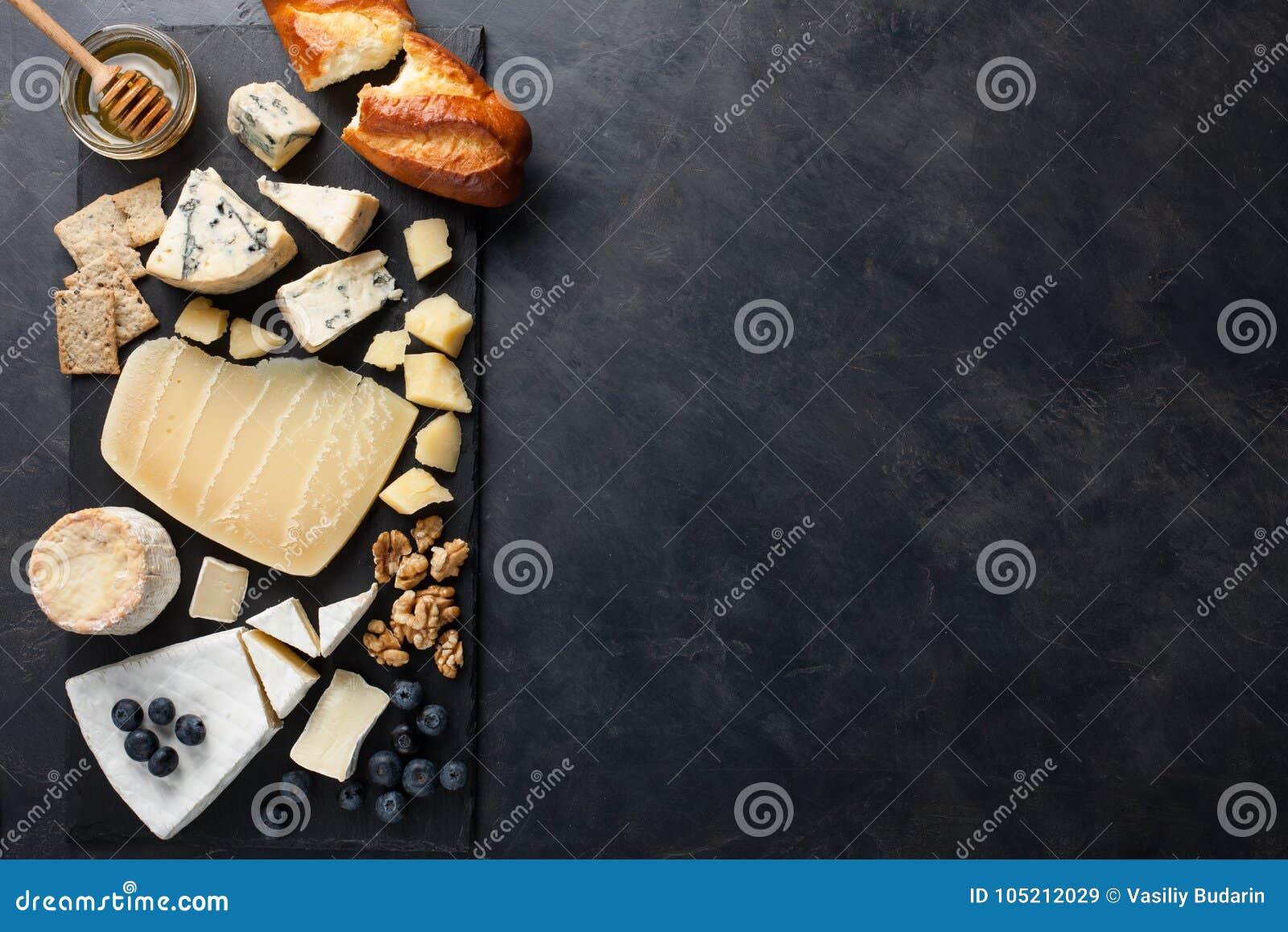 Δοκιμάζοντας πιάτο τυριών σε ένα σκοτεινό πιάτο πετρών Τρόφιμα για το κρασί και ρομαντική ημερομηνία, λιχουδιές τυριών σε ένα μαύ