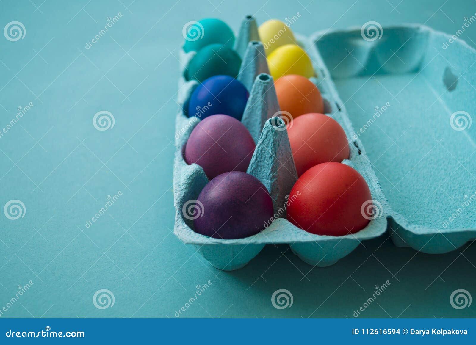 Δονούμενα βαμμένα χέρι ζωηρόχρωμα αυγά Πάσχας σε ένα κιβώτιο αυγών χαρτονιού που αντιμετωπίζεται