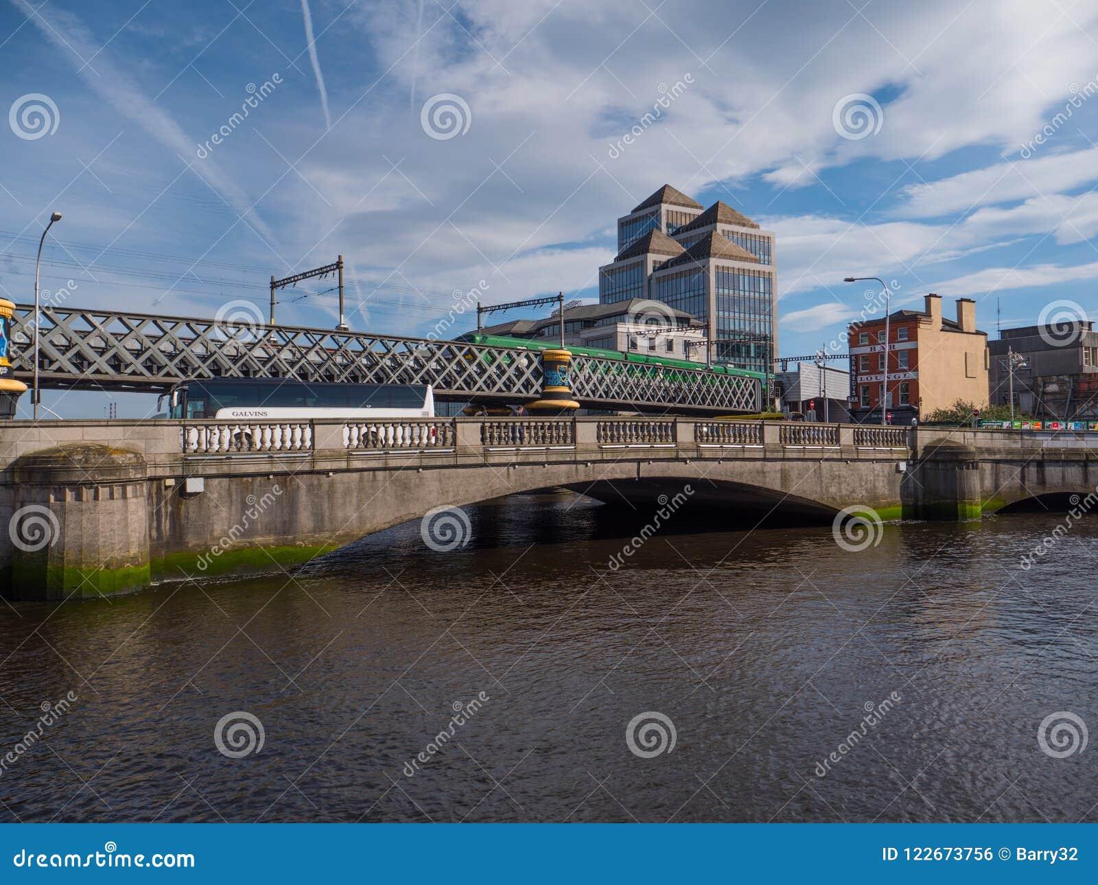 Δουβλίνο, Ιρλανδία - γέφυρα άκρης Liffey ποταμών, και γέφυρα ραγών με το τραίνο ΒΕΛΩΝ
