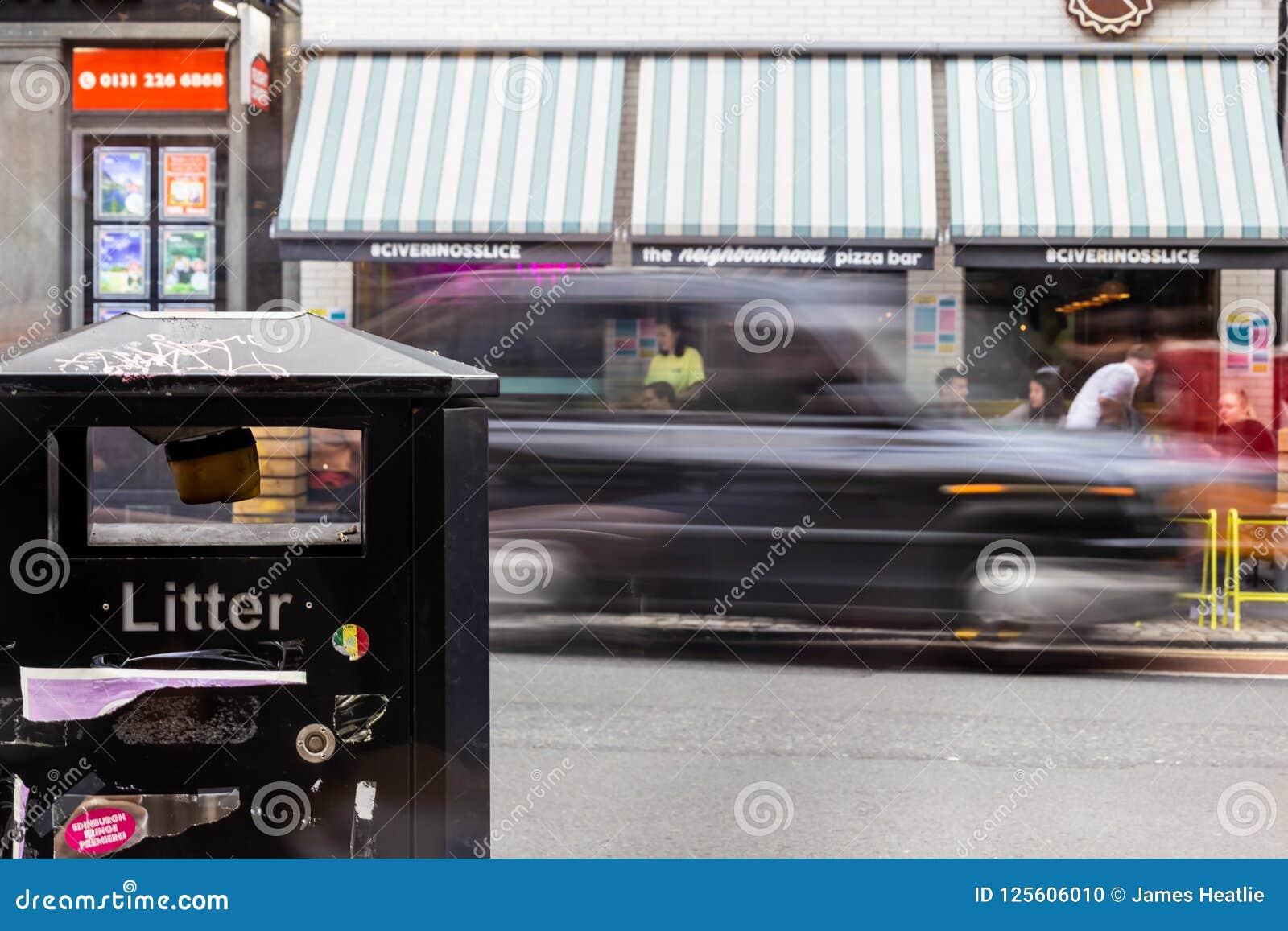Δοχείο απορριμάτων στο πρώτο πλάνο με το μαύρο αμάξι που περνά από πίσω