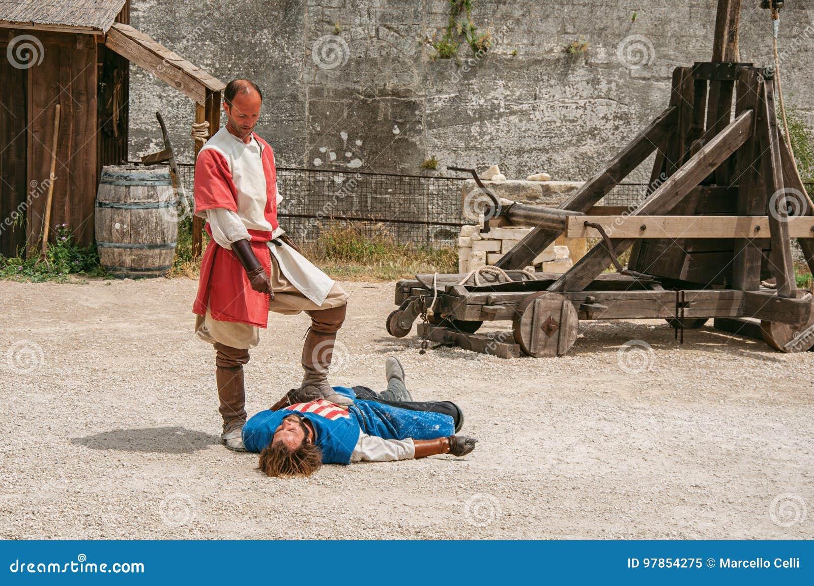 Δράστες που κάνουν μια θεατρική οργάνωση ως μεσαιωνικούς μαχητές στο κάστρο της baux-de-Προβηγκίας