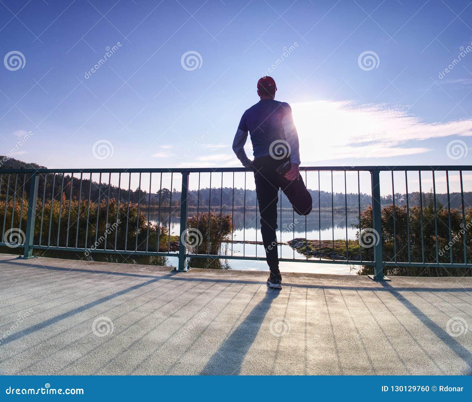 Δρομέας που κάνει την τεντώνοντας άσκηση στη γέφυρα Ένα ενεργό νευρικό άτομο