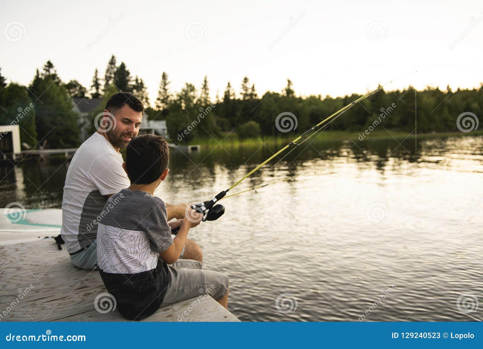 Δροσεροί μπαμπάς και γιος που αλιεύουν στη λίμνη