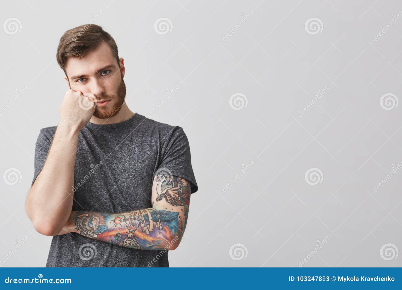 Δυστυχισμένος ελκυστικός νεαρός άνδρας με τη γενειάδα και διαστισμένο κεφάλι εκμετάλλευσης βραχιόνων με το χέρι, που τρυπιέται με