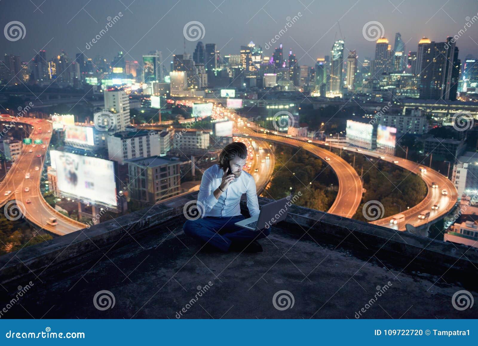 Δυτικός επιχειρηματίας που χρησιμοποιεί το τηλέφωνο και το lap-top με το υπόβαθρο πόλεων