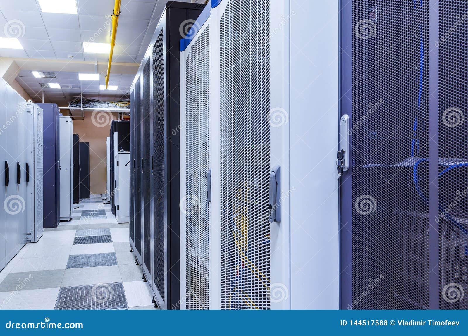 Δωμάτιο με τις σειρές του υλικού κεντρικών υπολογιστών στο μεγάλο σύγχρονο διάδρομο κέντρων δεδομένων Τεχνικοί εξοπλισμός και υπε