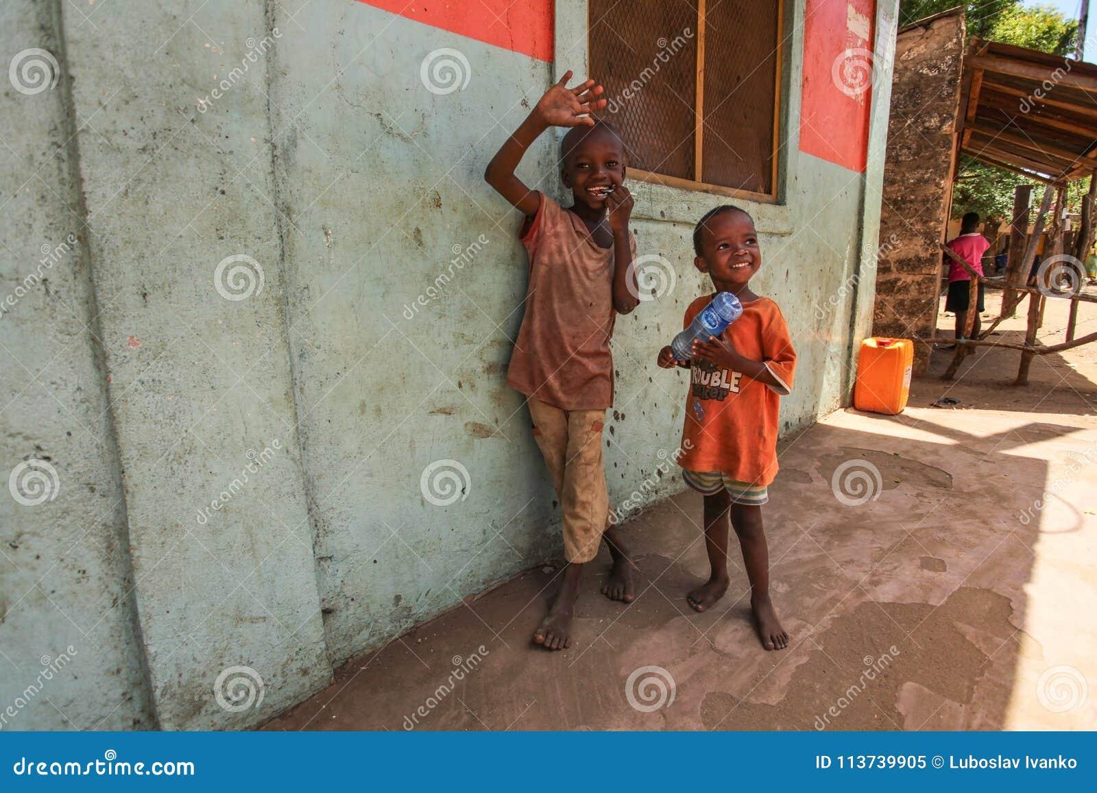 Δύο άγνωστα μικρά αγόρια, στεμένος δίπλα στον τοίχο, χαμογελώντας και κυματίζοντας στον τουρίστα που επισκέπτεται την τοπική τρώγ