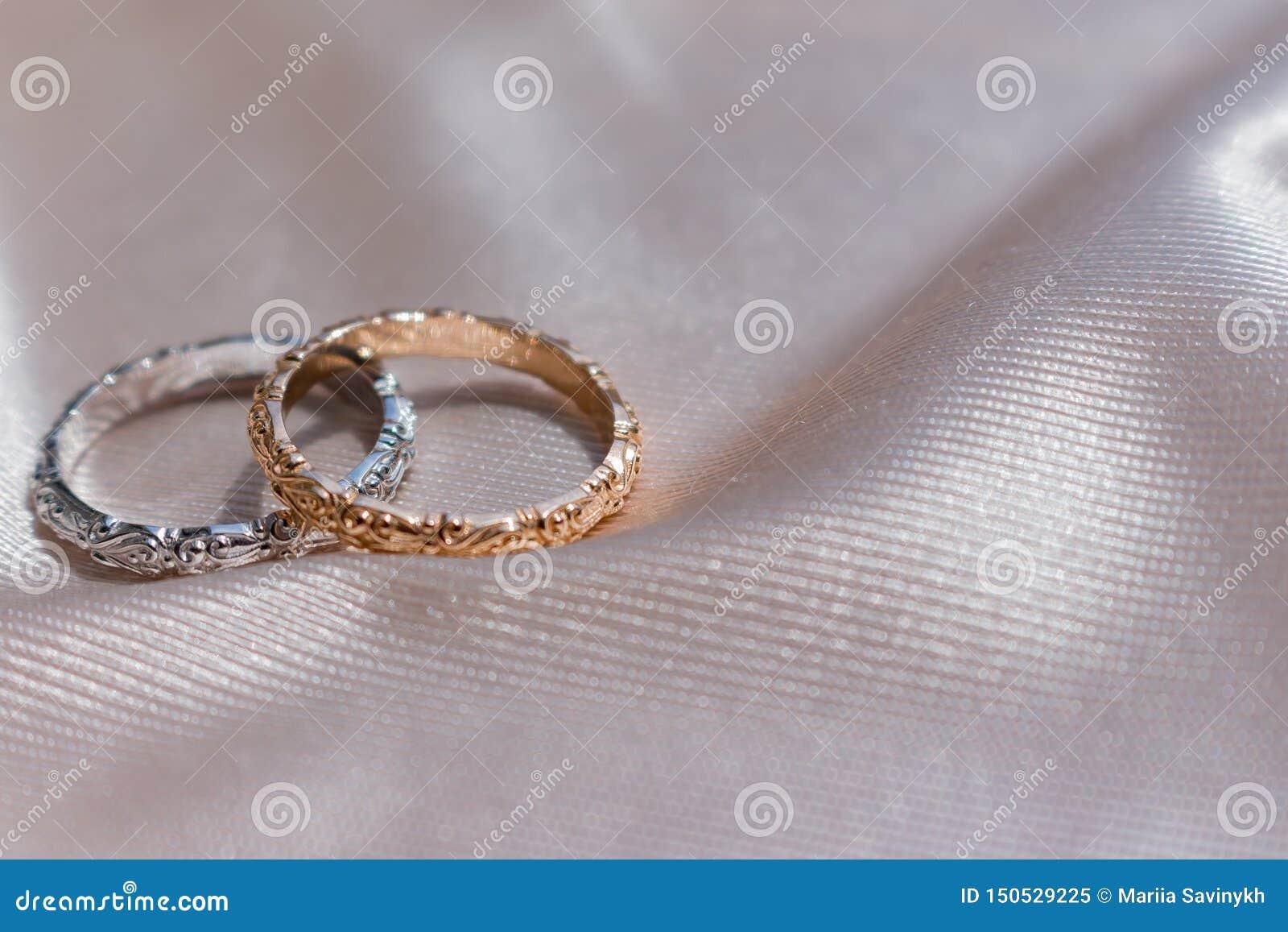 Δύο άσπρα και ρόδινα χρυσά γαμήλια δαχτυλίδια στο υπόβαθρο σατέν, έννοια γαμήλιων δαχτυλιδιών
