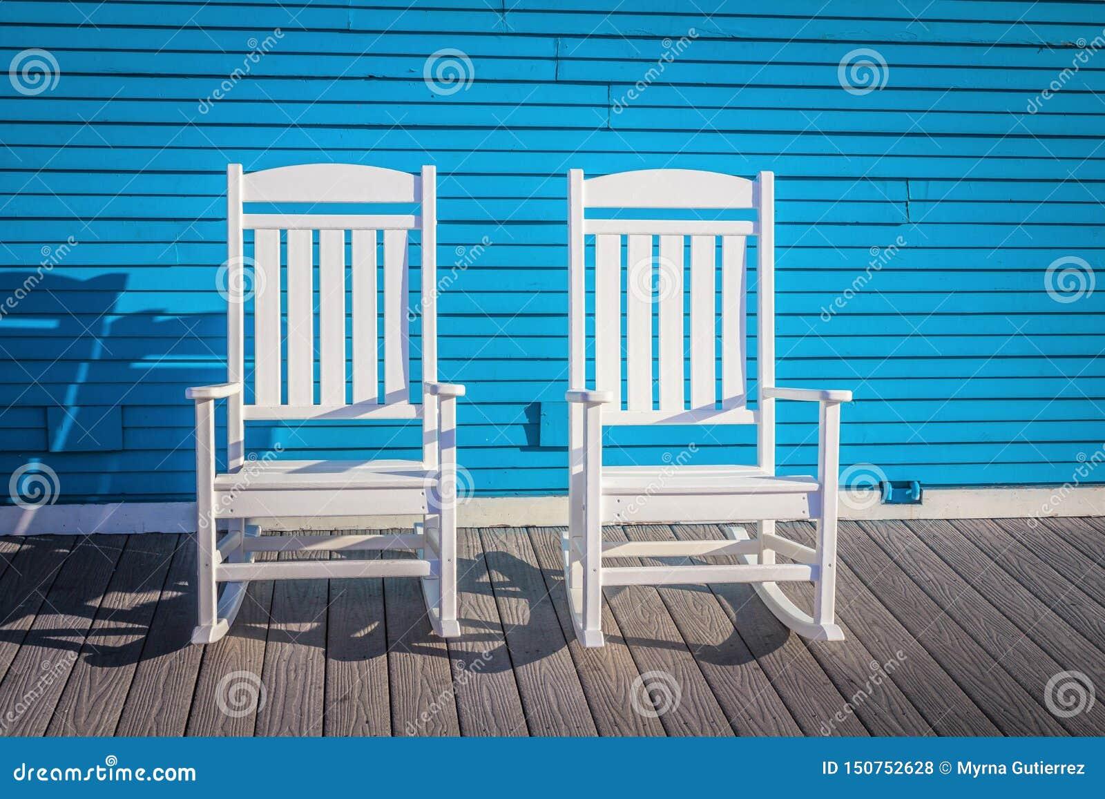 Δύο άσπρες υπαίθριες ξύλινες καρέκλες ενάντια στον μπλε τοίχο