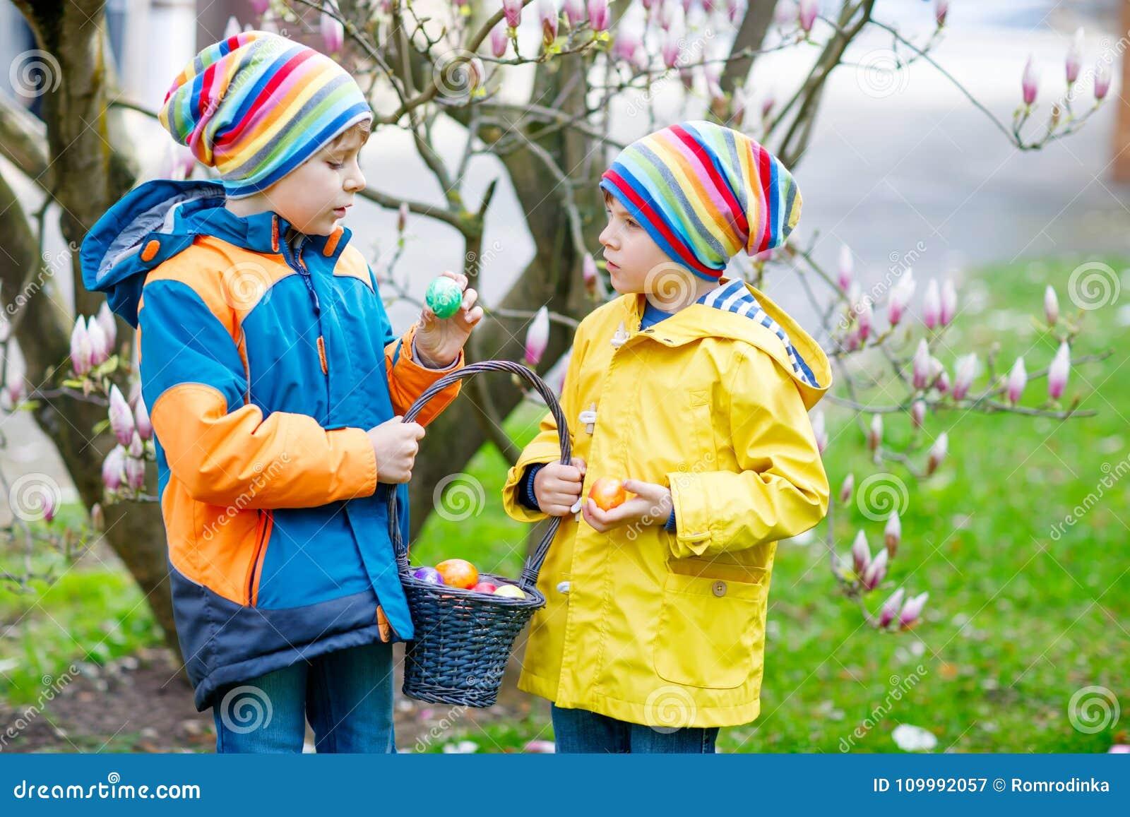 Δύο αγόρια και φίλοι παιδάκι που κατασκευάζουν το παραδοσιακό αυγό Πάσχας να κυνηγήσει