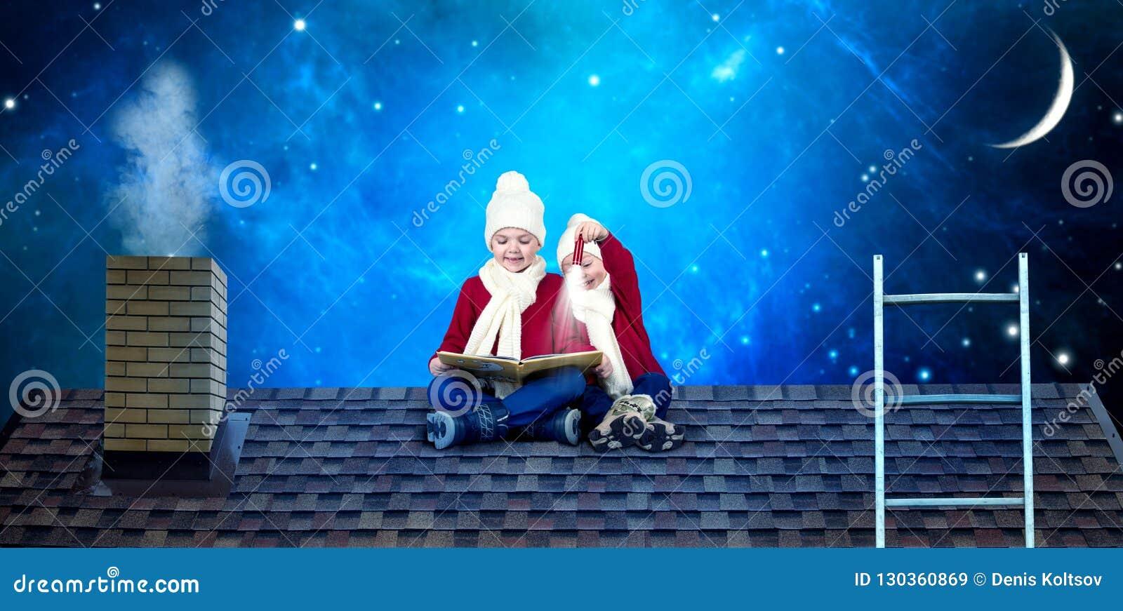 Δύο αδελφοί κάθονται στη νύχτα Χριστουγέννων στη στέγη και διαβάζουν ένα βιβλίο με τα παραμύθια Σε αναμονή για τα θαύματα Χριστου