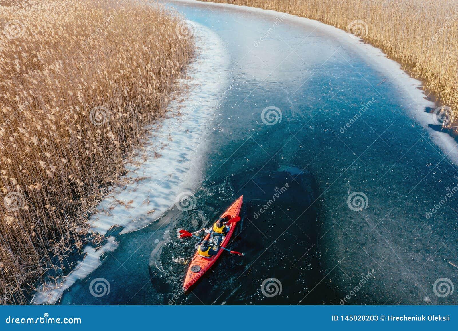 Δύο αθλητικά επιπλέοντα σώματα ατόμων σε μια κόκκινη βάρκα στον ποταμό