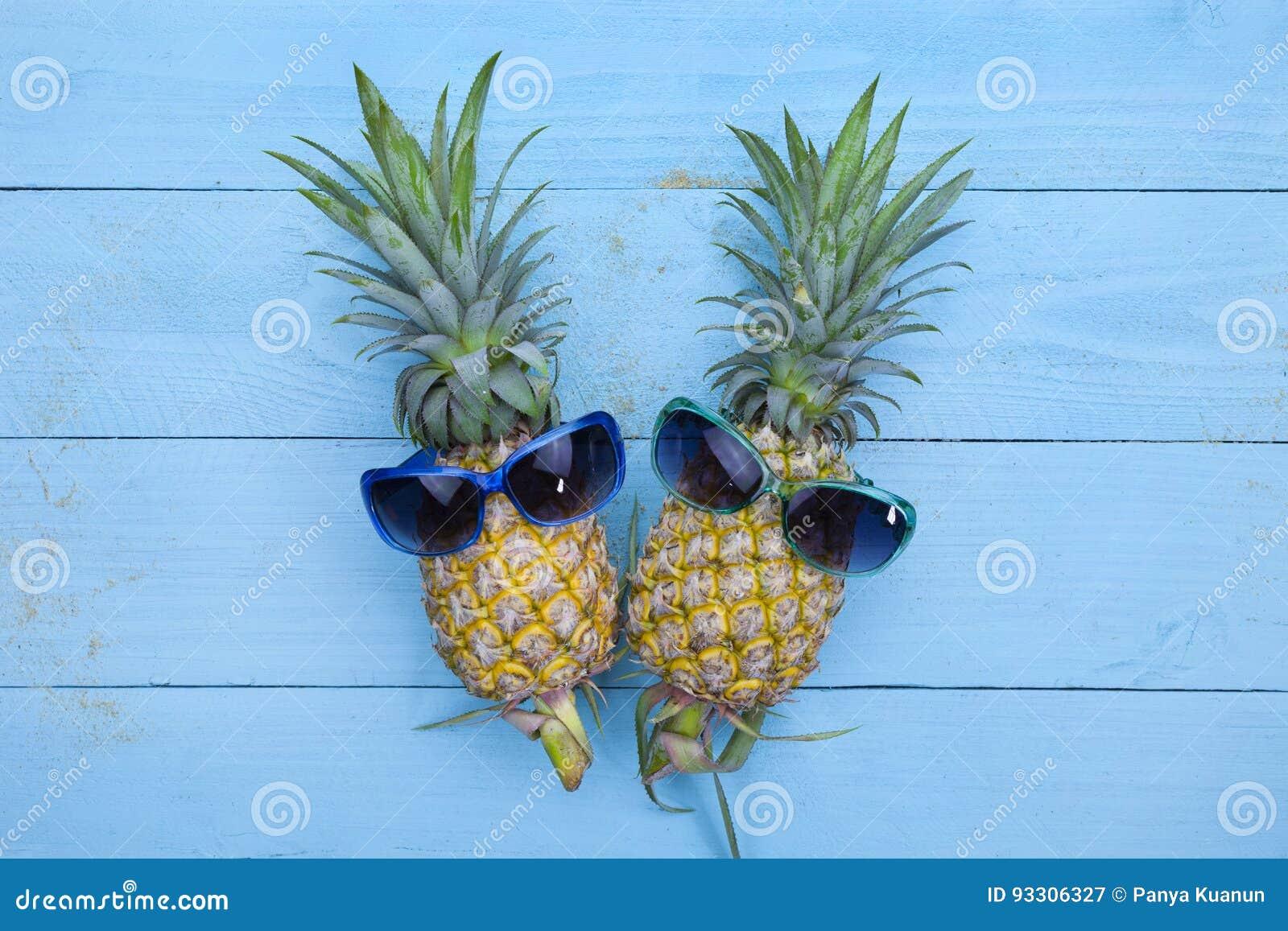 Δύο ανανάδες στα μοντέρνα γυαλιά ηλίου στο μπλε ξύλινο backgrou