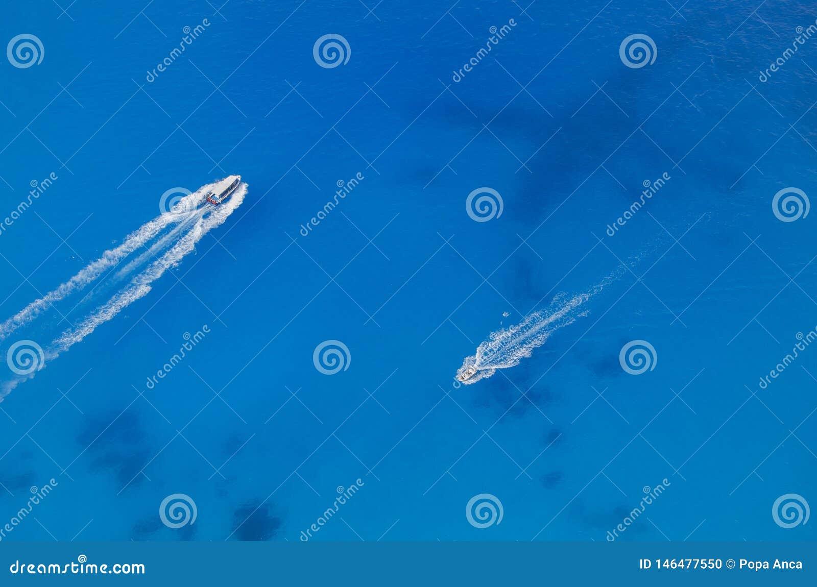 Δύο αντίθετες βάρκες στο σαφές μπλε νερό