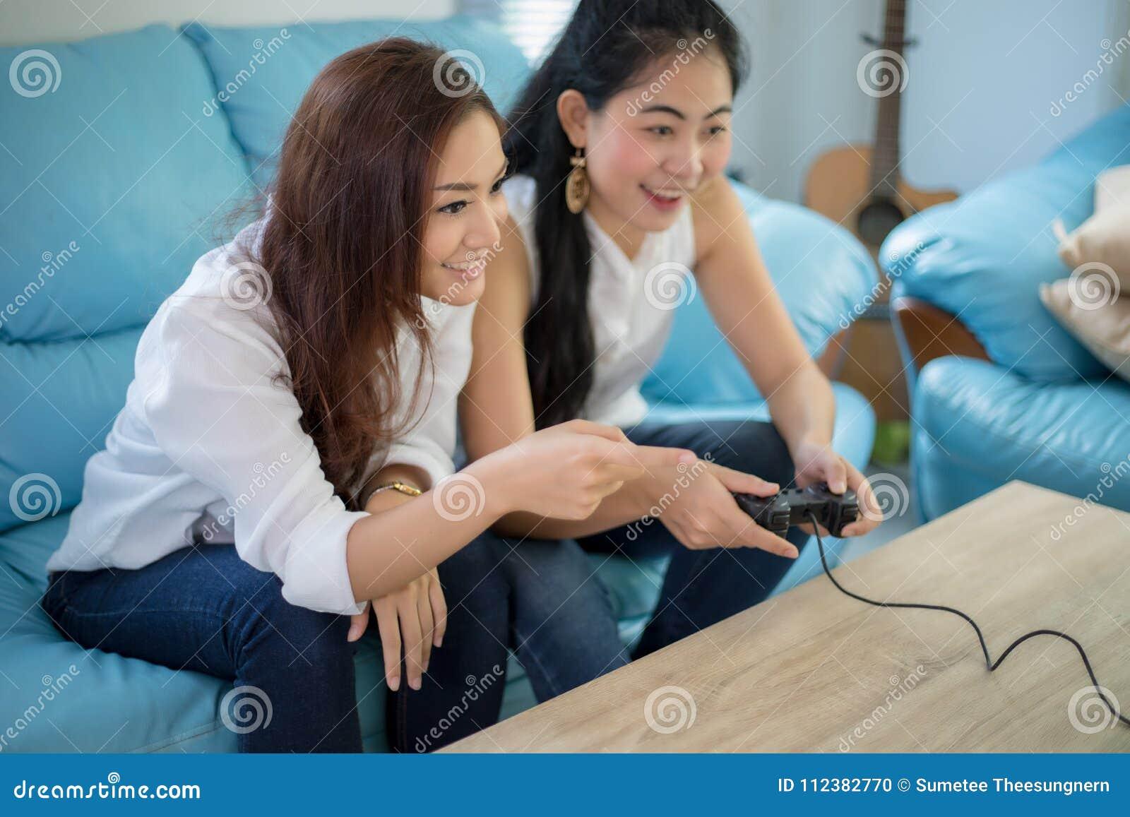 Δύο ανταγωνιστικοί φίλοι γυναικών που παίζουν τα τηλεοπτικά παιχνίδια και το συγκινημένο εκτάριο