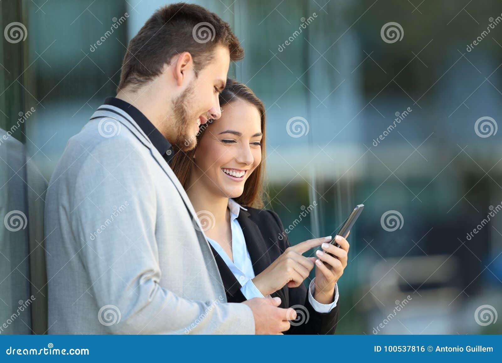 Δύο ανώτεροι υπάλληλοι που χρησιμοποιούν ένα κινητό τηλέφωνο στην οδό