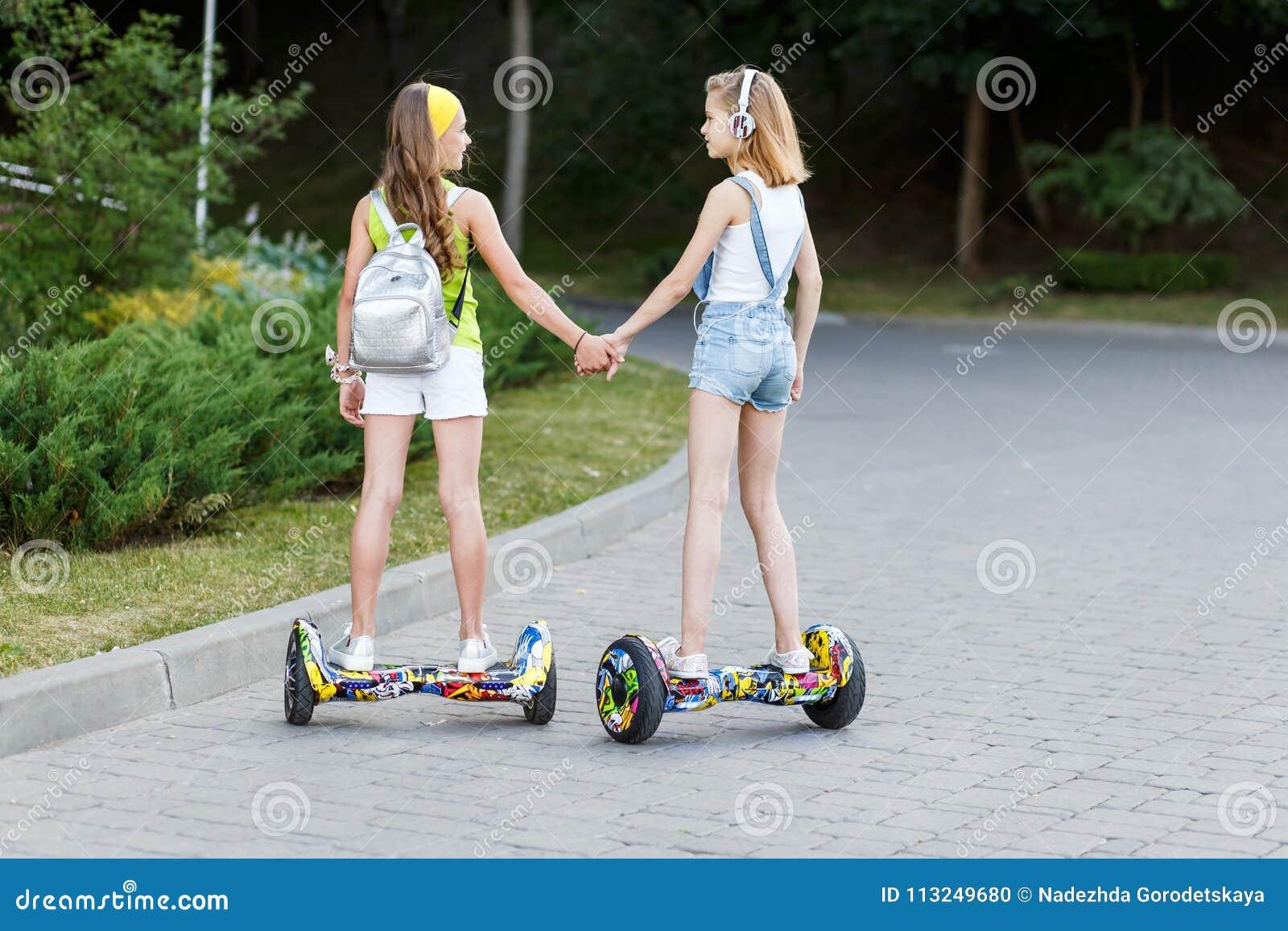 Δύο αρκετά ευτυχή κορίτσια που οδηγούν αιωρούνται τον πίνακα ή gyroscooter υπαίθρια στο ηλιοβασίλεμα το καλοκαίρι Ενεργός έννοια