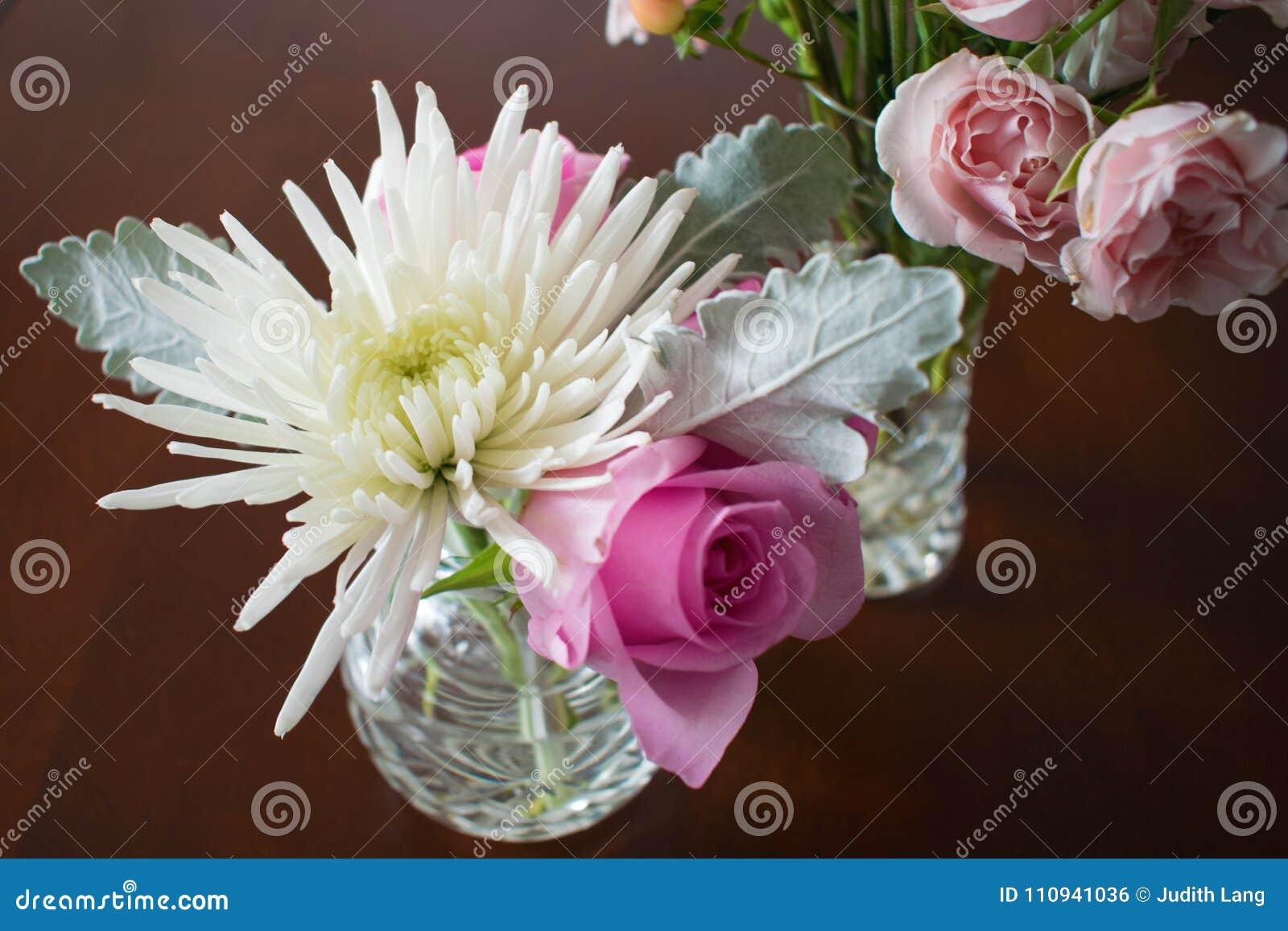 Δύο βάζα κρυστάλλου με τα λουλούδια στο σκοτεινό ξύλινο πίνακα