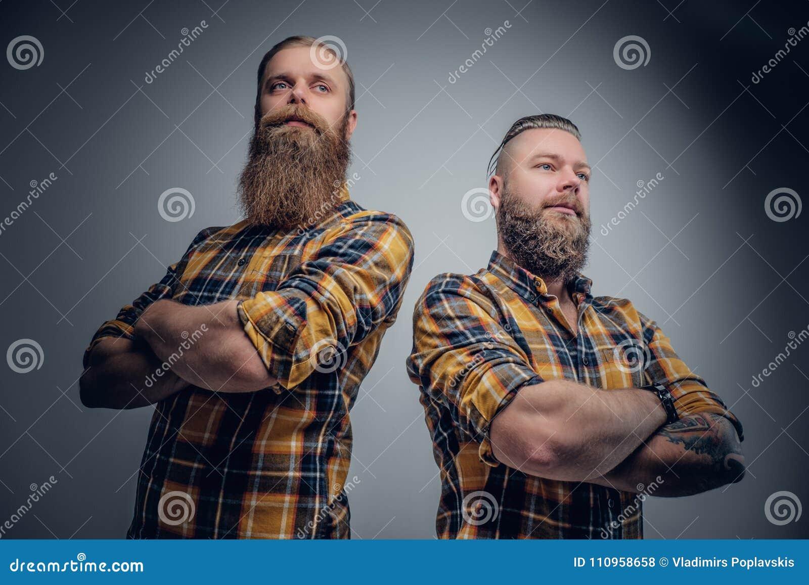 Δύο βάναυσα γενειοφόρα άτομα έντυσαν σε ένα πουκάμισο καρό