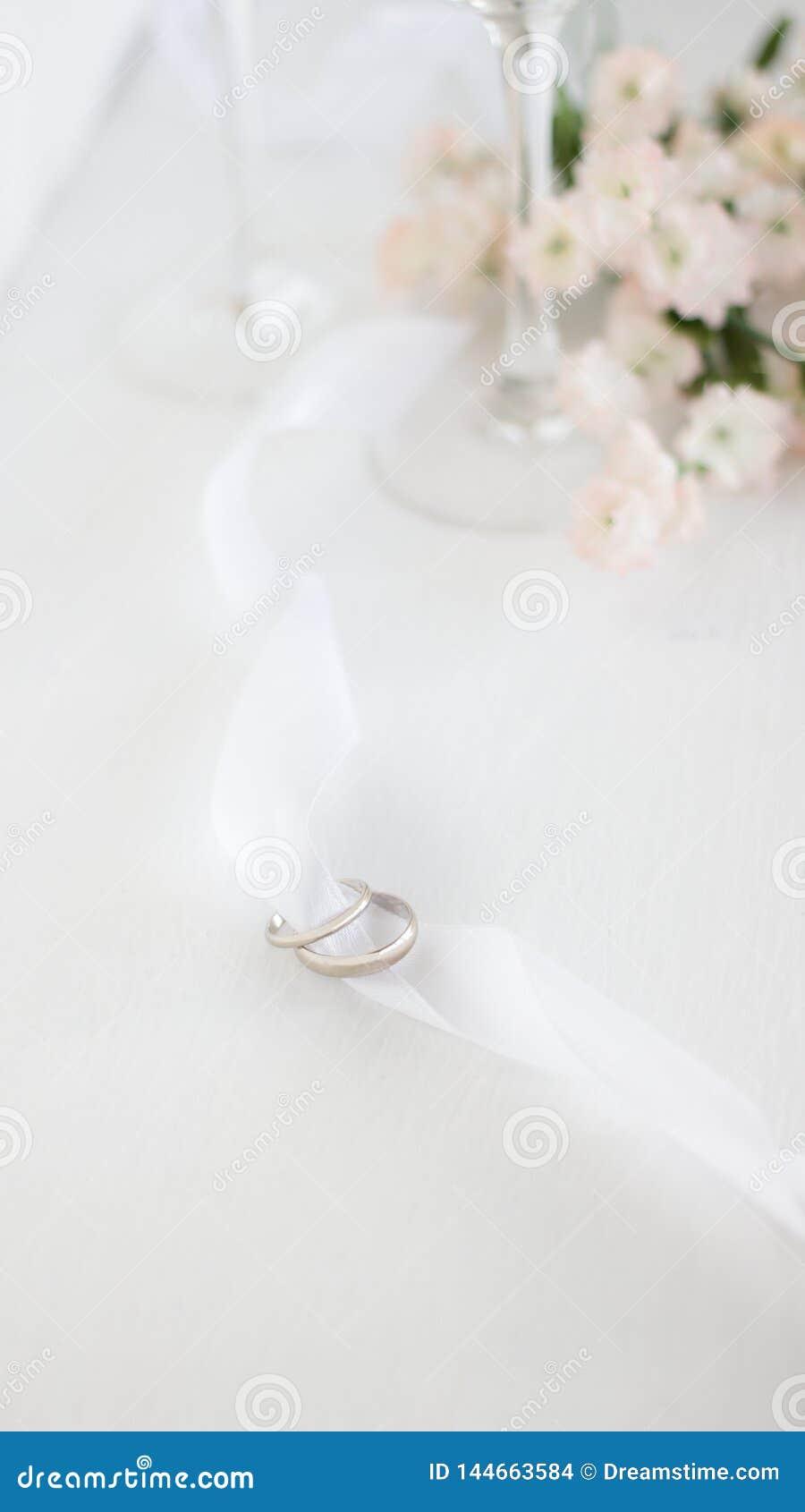 Δύο γαμήλια δαχτυλίδια στην άσπρη κορδέλλα Ελαφρύ υπόβαθρο θαμπάδων των λουλουδιών και champane των γυαλιών