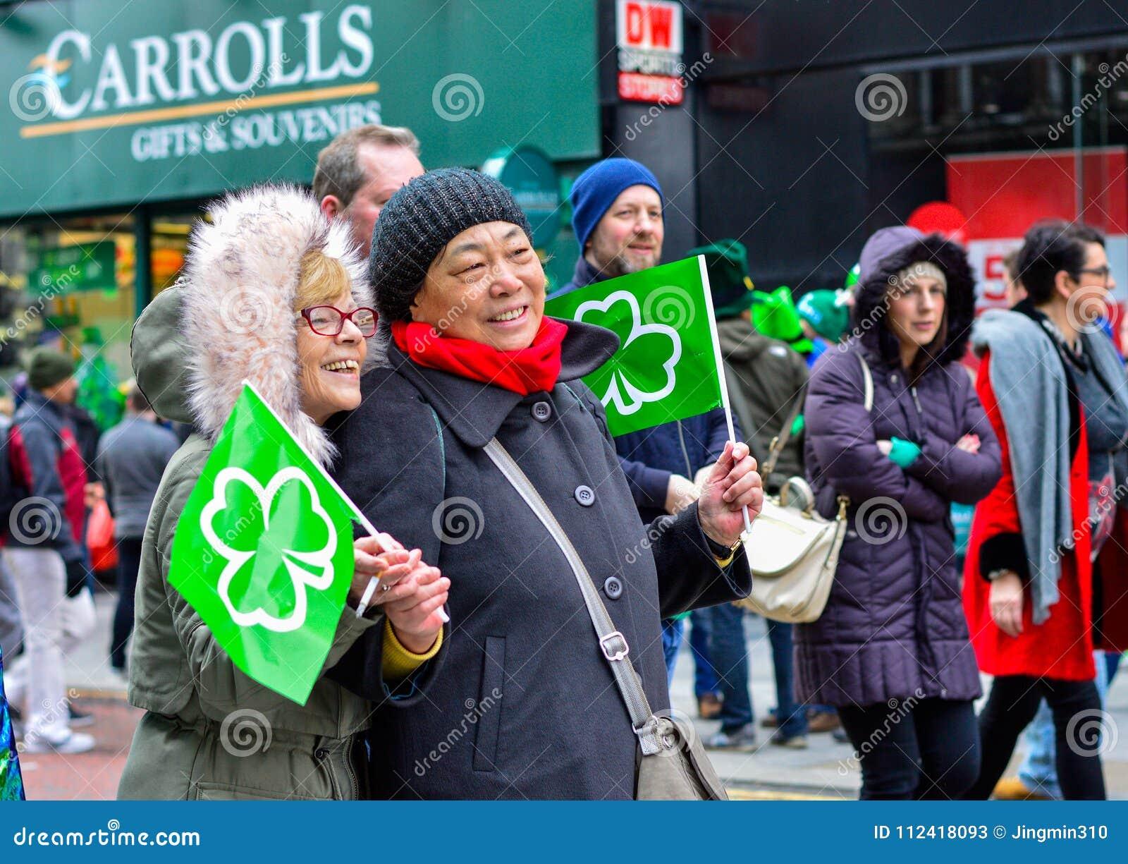 Δύο γυναίκες θέτουν για τη κάμερα στην παρέλαση ημέρας του ST Πάτρικ ` s στο κέντρο της πόλης του Μπέλφαστ