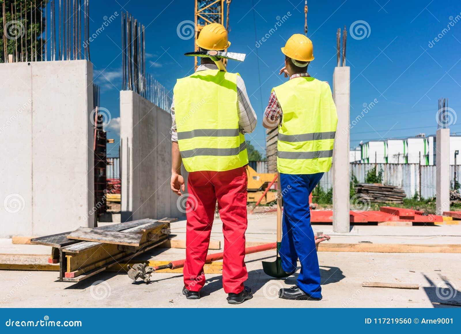 Δύο εργαζόμενοι που φορούν τον εξοπλισμό ασφάλειας προγραμματίζοντας την εργασία