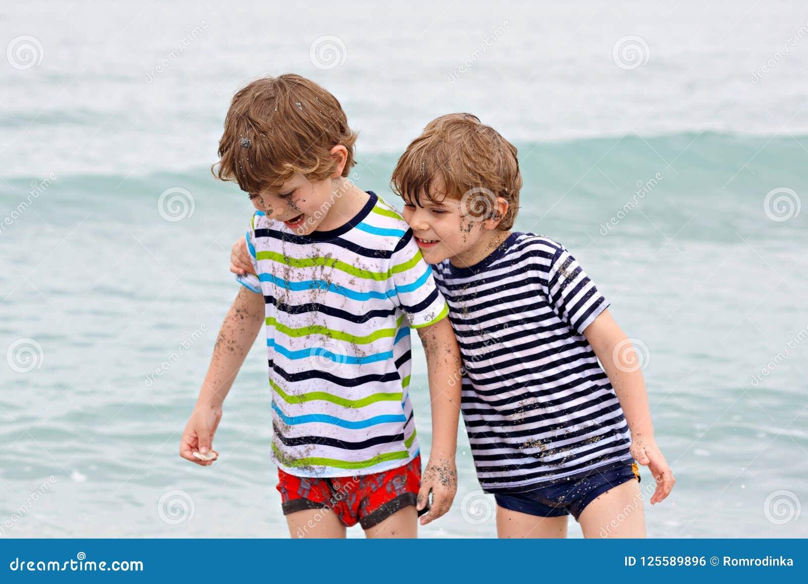 Δύο ευτυχή αγόρια παιδάκι που τρέχουν στην παραλία του ωκεανού Αστεία παραγωγή παιδιών, αμφιθαλών, διδύμων και καλύτερων φίλων