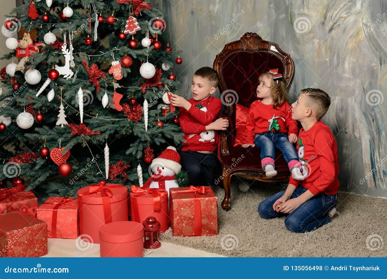 δύο ευτυχή αγόρια στην εορταστική διαφορά των δέντρων έλατου εξετάζουν τα δώρα