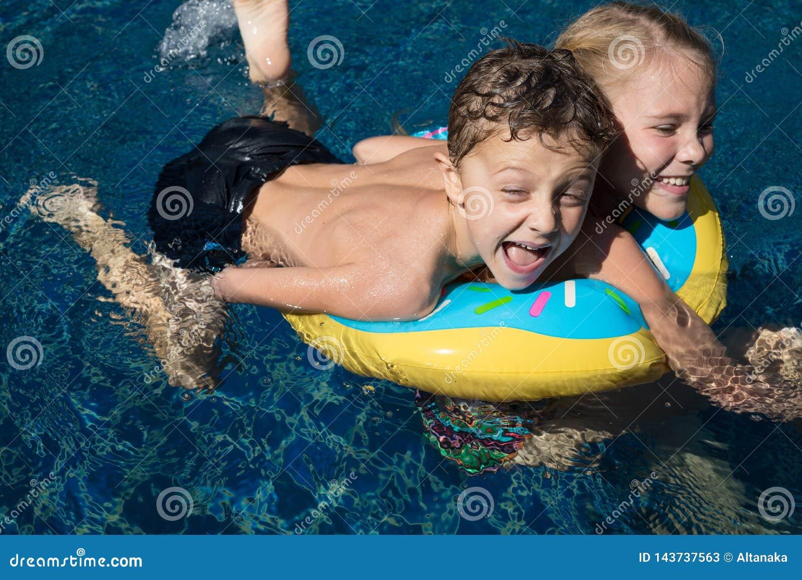 Δύο ευτυχή παιδιά που παίζουν στην πισίνα στο χρόνο ημέρας