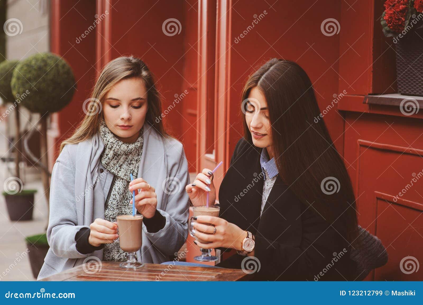 Δύο ευτυχείς φίλοι κοριτσιών που μιλούν και που πίνουν τον καφέ στην πόλη φθινοπώρου στον καφέ