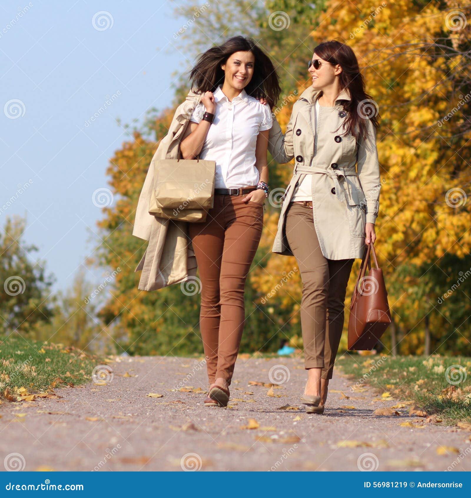 Δύο ελκυστικές γυναίκες με τα φύλλα σφενδάμου φθινοπώρου στο πάρκο στο OU πτώσης