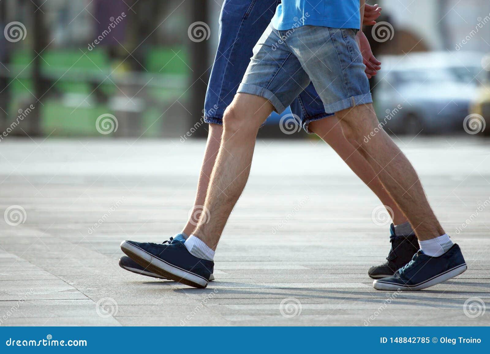 Δύο ζευγάρια των ποδιών που περπατούν μαζί τα άτομα