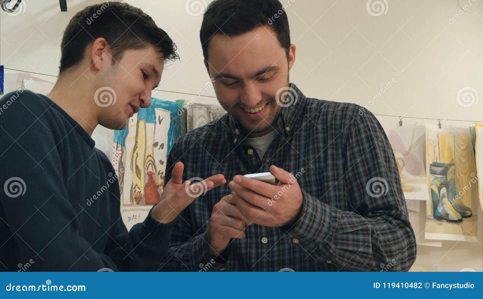 Δύο θετικοί σπουδαστές τέχνης που γελούν σε κάτι στο τηλέφωνο