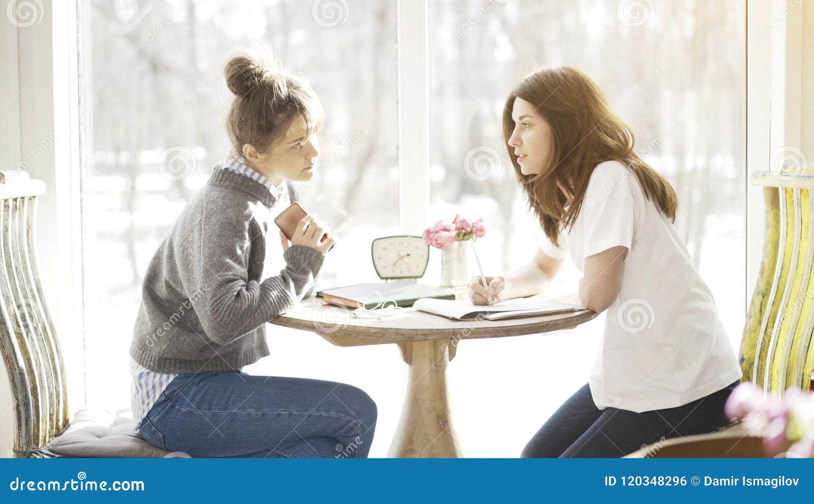 Δύο θηλυκοί σπουδαστές φίλων που διοργανώνουν μια σοβαρή συζήτηση