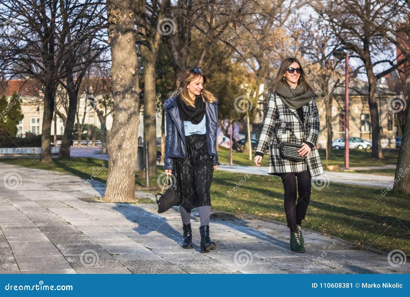 Δύο θηλυκοί φίλοι που έχουν τον περίπατο στο πάρκο