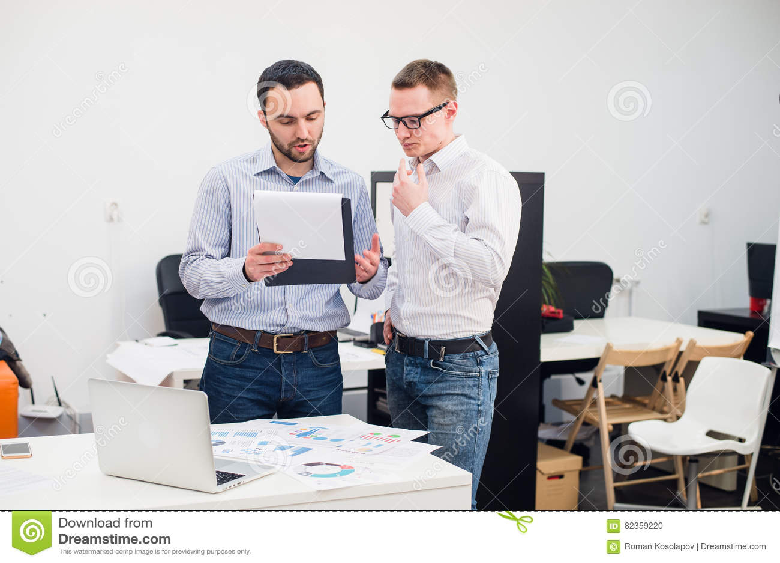 Δύο καυκάσιοι διοικητικοί συνεργάτες στην περιστασιακή ένδυση που διοργανώνει μια επιχειρησιακή συζήτηση στην αρχή