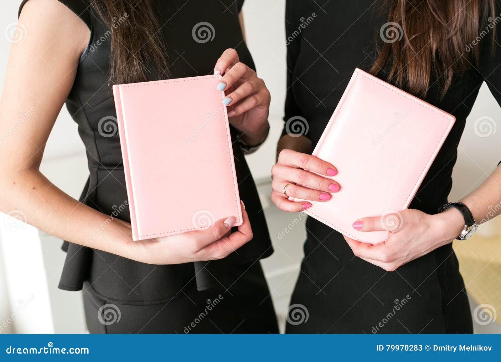 Δύο κορίτσια κρατούν τα επιχειρησιακά σημειωματάρια διαθέσιμα